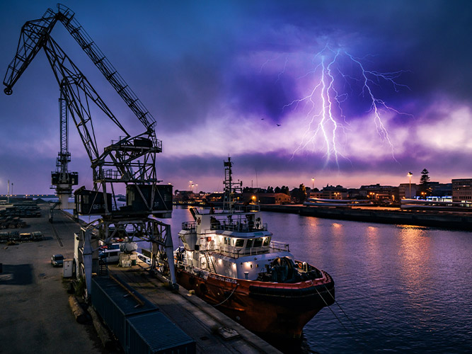 Night view of a shipping port with lightning and thunderstorm nearby