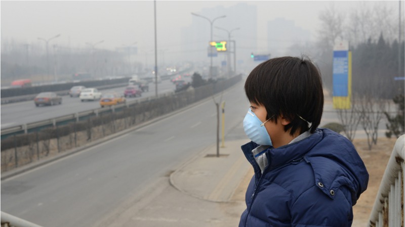A boy in a face-mask and Smog in the city