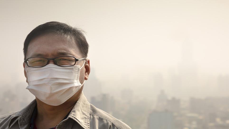 A man wearing a mask due to the smog in a city