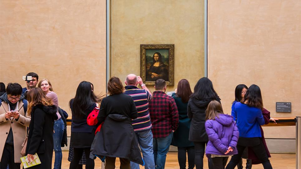 Mona Lisa in Louvre, Paris, surrounded by a crowd