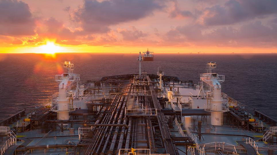 Oil tanker sailing towards a sunset