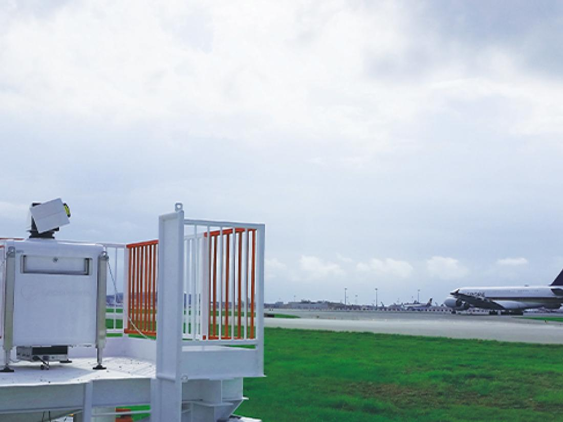 Close-up of WindCube Scan wind lidar with air traffic control tower
